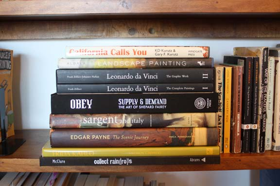 A stack of books lays horizontally for aesthetics and space maximizing. Can you tell someone is an artist?